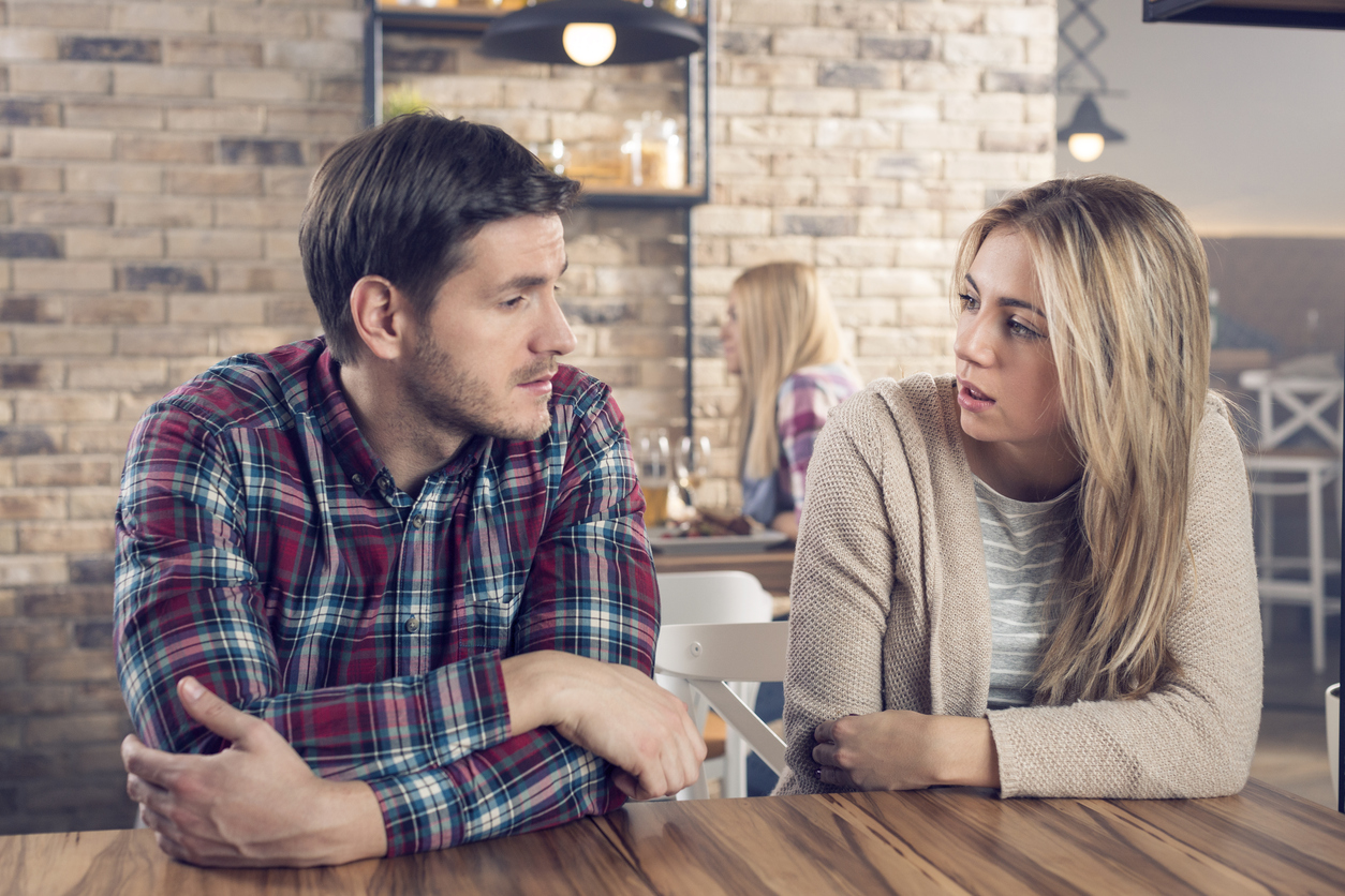 Young couple having a serious conversation in a bar.