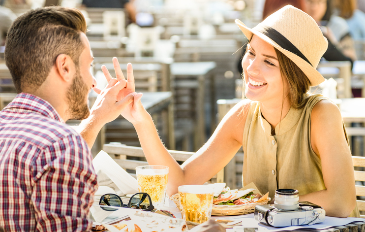 Couple on a date smiling, holding hands