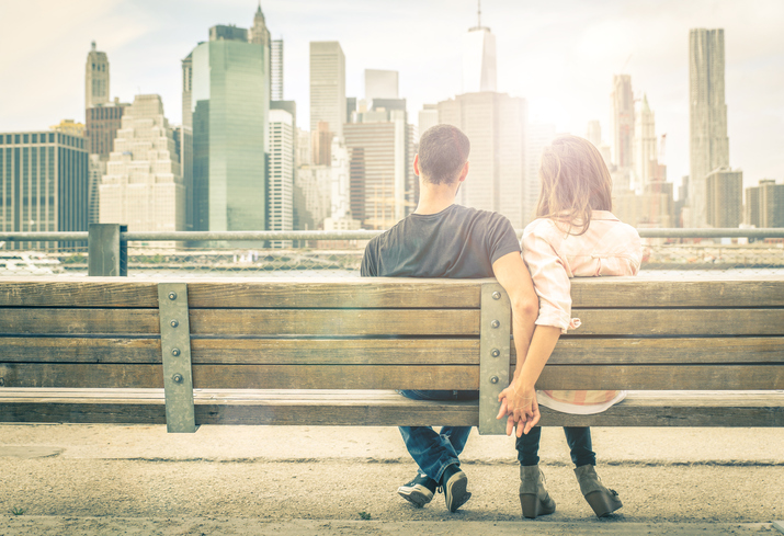 couple relaxing on New york bench in front of the skyline at sunset time. concept about love,relationship, and travel