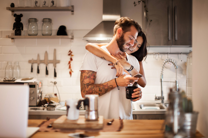 Young couple at home using smartphone - Morning breakfast time