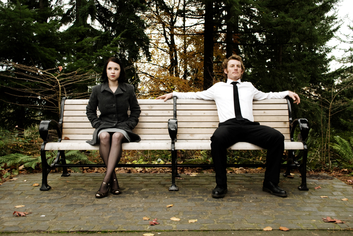 fall scene of a girl and guy sitting on opposite sides of a park bench, looking off in different directions
