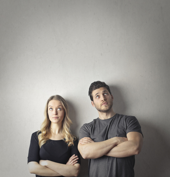 Couple is standing next to each other with their arms crosses