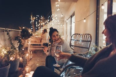 Young smiling woman enjoying in good wine and great company on the open terrace of her loft apartment