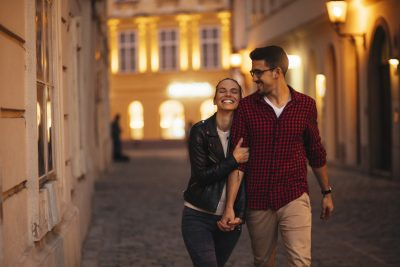 Happy young couple walkng in a beautiful city in the evening, passive-aggressive