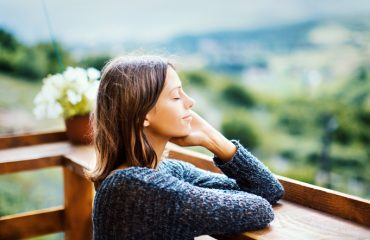 Young woman enjoying a fresh air on the mountain during summer morning.
