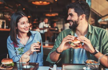 Happy loving couple enjoying breakfast date in a cafe. Love, dating, food, lifestyle concept