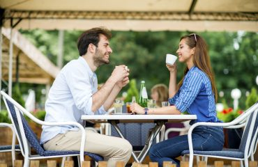 Loving couple at coffee house having coffee date and chatting