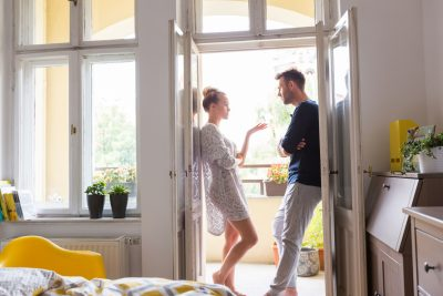 Couple agruingm standing with bad body language in the open window at home in the morning.