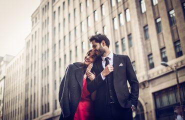 professional dressed couple in love walking down the street early in spring.