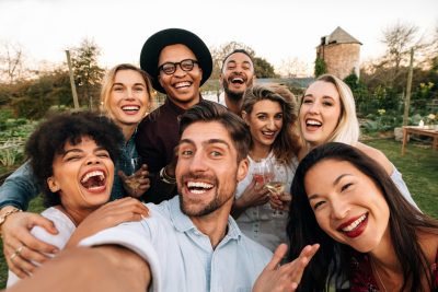 Friends chilling outside taking group photos and smiling. Laughing young people standing together outdoors and taking selfie.