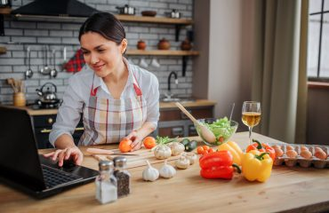 Cheerful adult woman sit at table in kitchen. She typing on keyboard and look on screen. Woman cook food