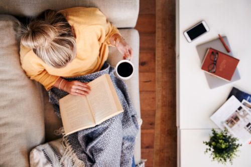 Overhead Shot Looking Down On Woman At Home Lying On Reading Book And Drinking Coffee for self-care