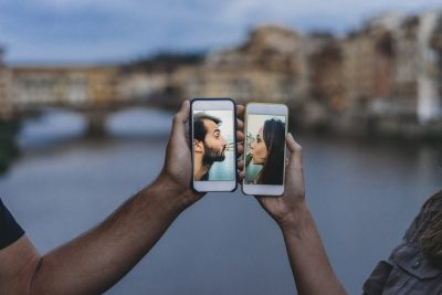 Conceptual shot of a young adult couple kissing via mobile phone on dating apps