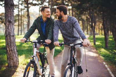Beautiful gay couple at sunny day riding bike at park. They took a break to rest. Autumn sunny day.