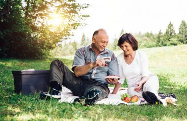 Elderly couple having picnic on the mountain meadow near forest after divorce