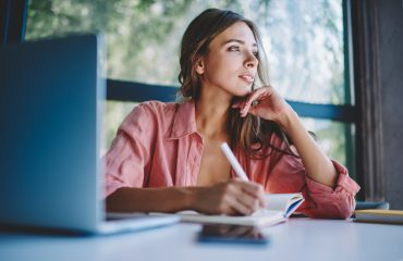 Pondering young woman looking away while making notes and thinking on creative ideas for developing own internet website.Thoughtful hipster student writing down information in notepad sitting at table looking at dealbreakers