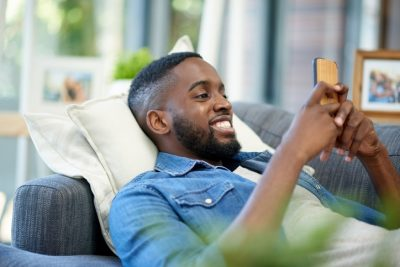 Shot of a young man using a cellphone while relaxing at home texting