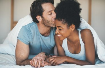 Shot of an affectionate middle aged man kissing his wife on her forehead while relaxing on their bed at home. get relationship-confident