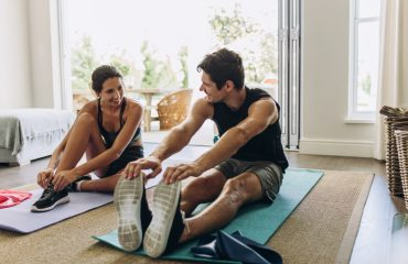 Couple exercising together. Man and woman in sports wear doing workout at home with their partner to achieve their core values