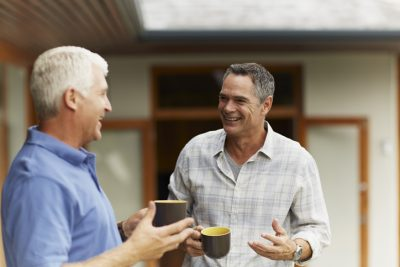 Happy male friends having coffee at yard maintaining friend relationship