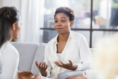 Young African American woman gestures while talking with a female therapist. The patient has a concerned expression on her face with her dating coach
