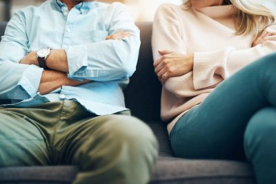 Cropped shot of an unrecognizable mature couple sitting on the sofa with their arms folded after an argument leading to divorce
