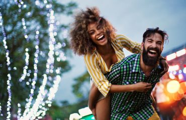 Young couple enjoying at music festival. They are laughing and looking at camera, relationship