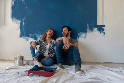 Portrait of a happy couple laughing while taking a break from painting - home improvement concepts in life