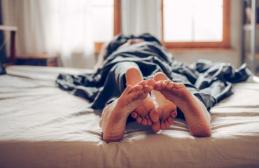 Adult couple's feet looking out of bed after one-night stand