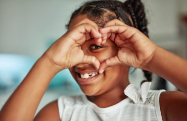 Cropped shot of a young girl forming a love heart shape with her hands