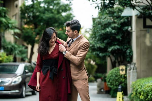 Handsome man helping his beautiful wife to dress up coat on the street, on beautiful day