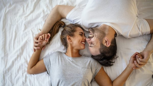 Guy and a girl in a cozy home environment. Happy man and woman lying in the bedroom stock photo. Top view of smiling young couple cuddling in bed in morning. Beautiful pair of lovers hug and kiss and happy