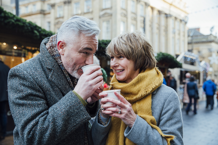 Mature couple are drinking hot drinks in a town christmas market dating