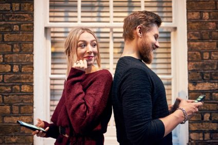 Shot of a young man and woman standing back to back and using their smartphones