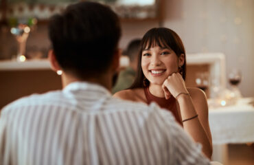 young woman smiling while on a date at a restaurant, flirting